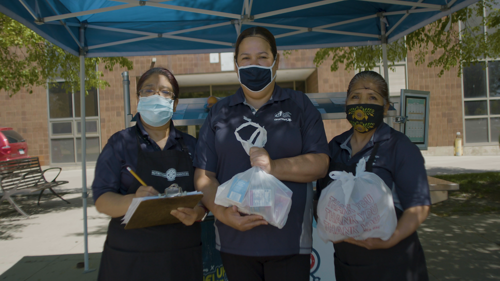 Three women in face masks and hair nets holding bags with food in them.
