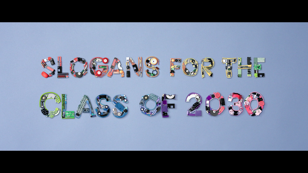 """The phrase """"Slogans for the class of 2030"""" written out using technical equipment in a rainbow of colors."""
