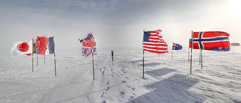 Image showing various countries flags stuck in the snow near the South Pole.