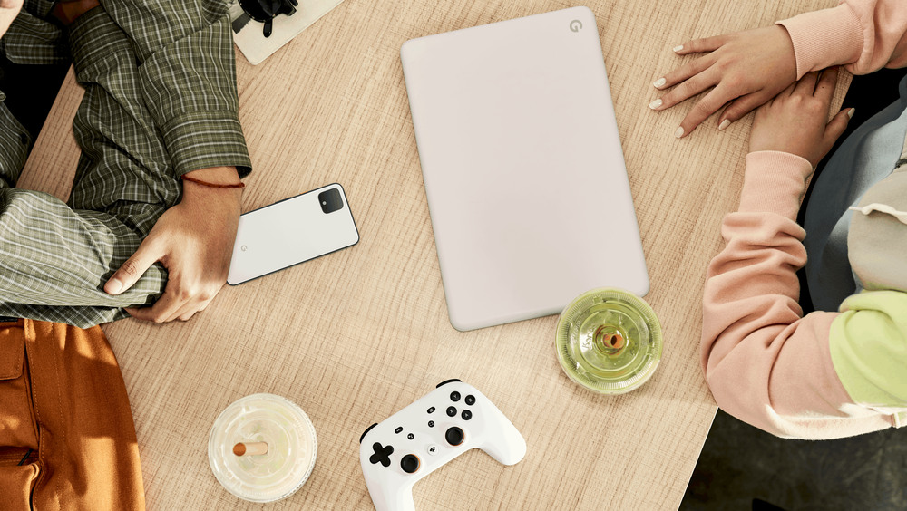 This image shows two people sitting at a table with a Stadia Controller, Pixel phone, and Google Chromebook.
