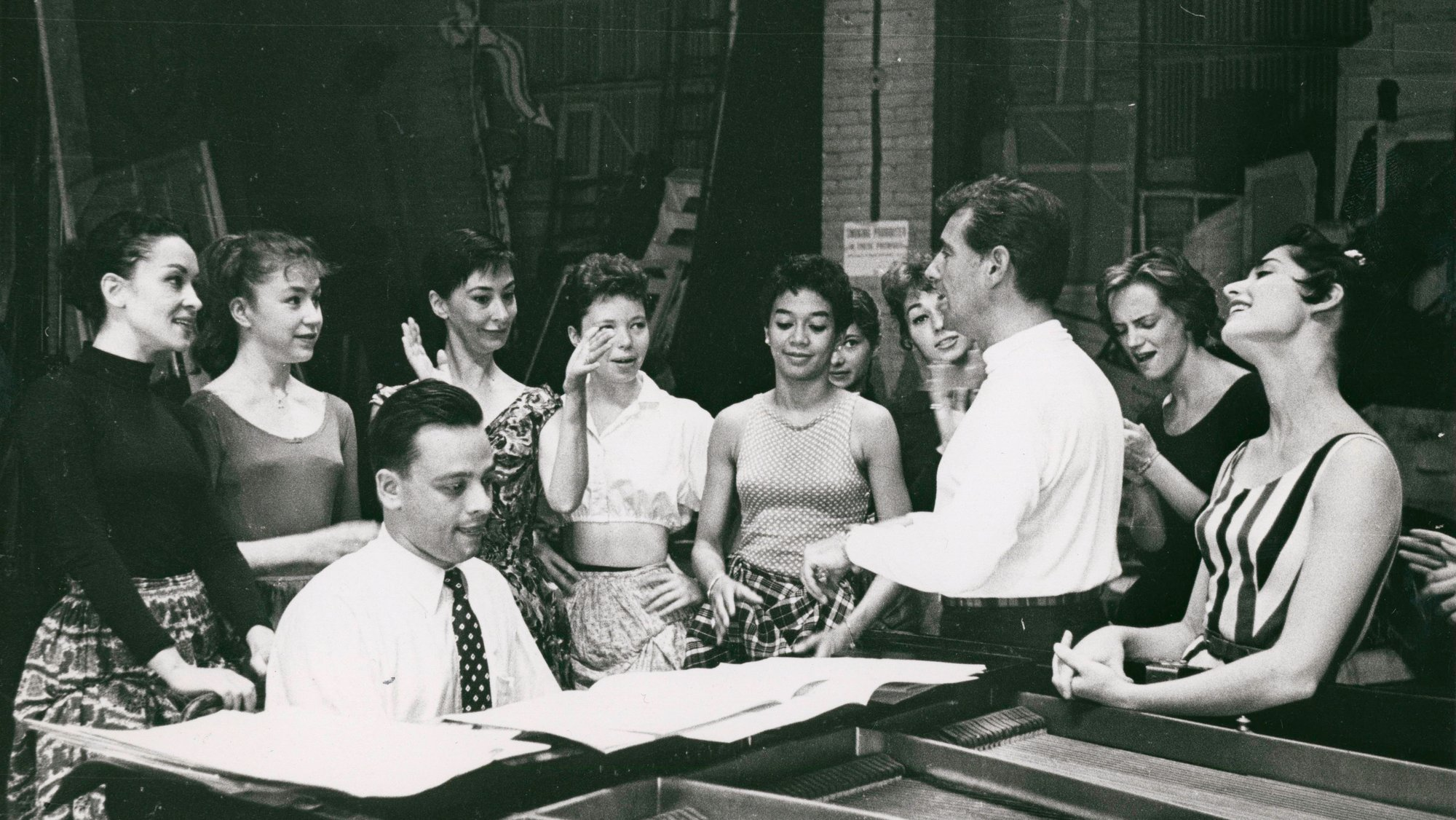 Stephen Sondheim on piano and Leonard Bernstein standing amongst female singers rehearsing for West Side Story (variant)_NYPL.jpg