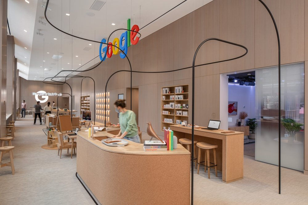 A person in a green sweater stands at a wooden desk inside Google's retail store.