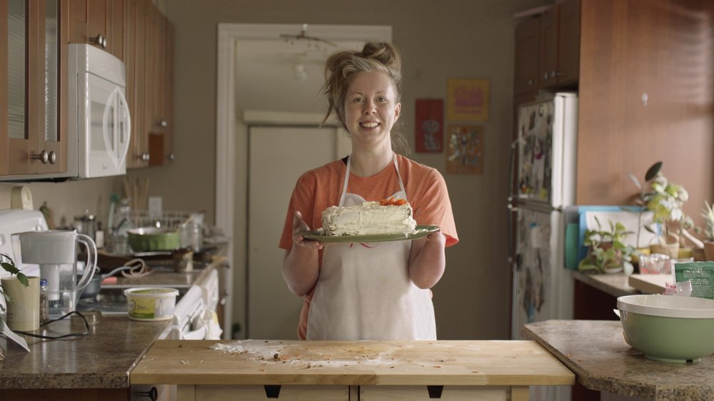 YouTube Creator, Alexis Hillyard, stands in her kitchen smiling holding up a white frosted cake with shaved orange carrots on a green plate over a counter with flour and carrot pieces
