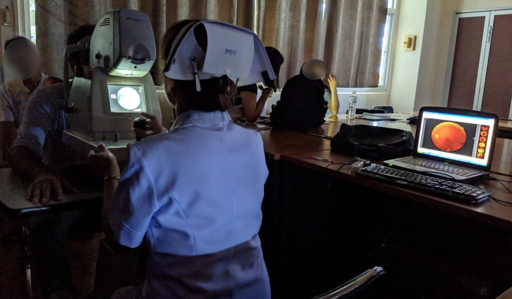 A nurse operates the fundus camera, taking images of a patient's retina.