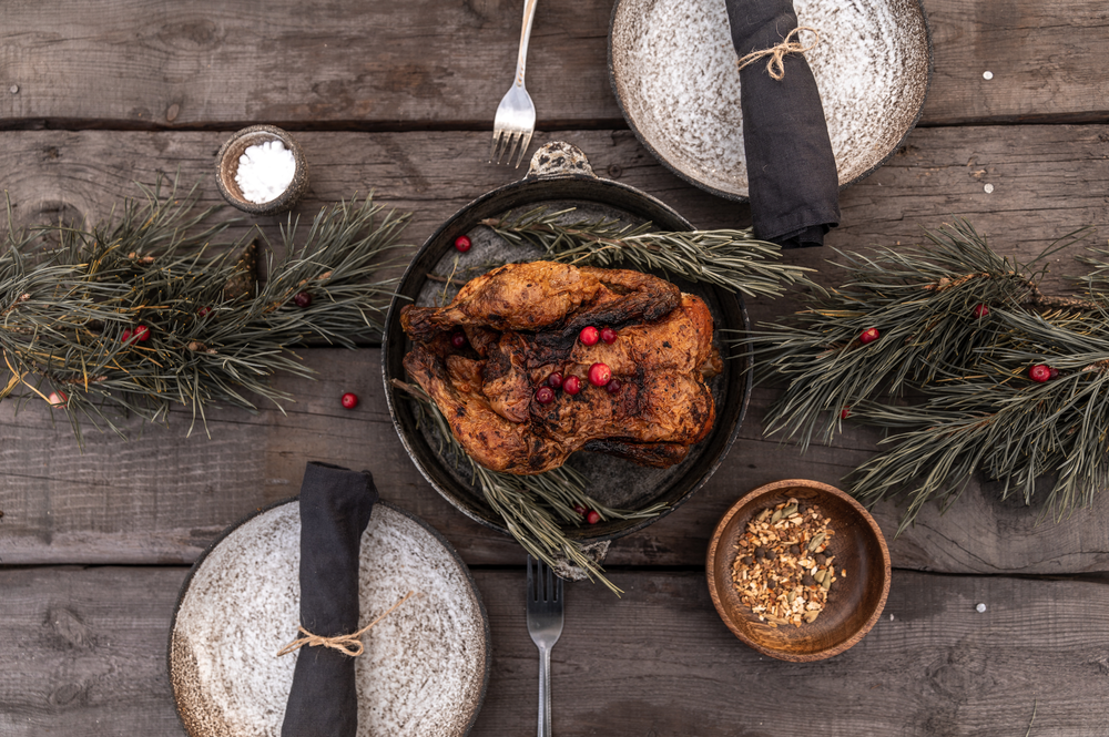 A table setting for two with holly and a roast turkey