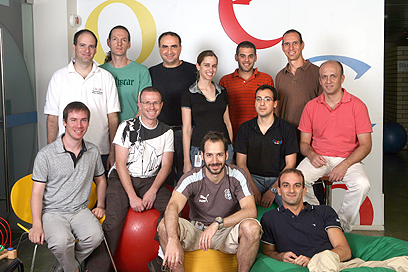 """The Google Trends team in Tel Aviv; they're gathered against a wall with the word """"Google"""" on it, smiling and looking into the camera."""