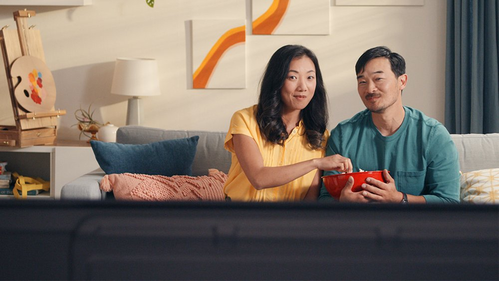 Two people sitting on a couch and sharing a bowl of popcorn while watching TV.
