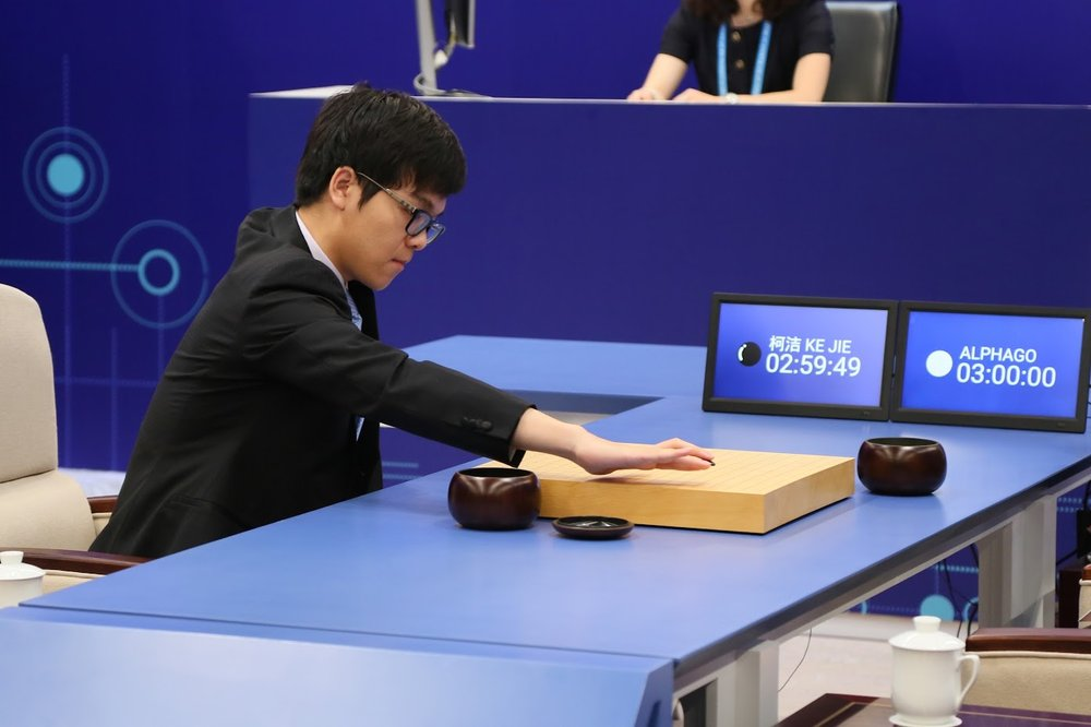 Grandmaster Ke Jie, wearing a suit and sitting on a white chair to the left of a blue table, leans forward to make a move on the board in his match against AlphaGo.