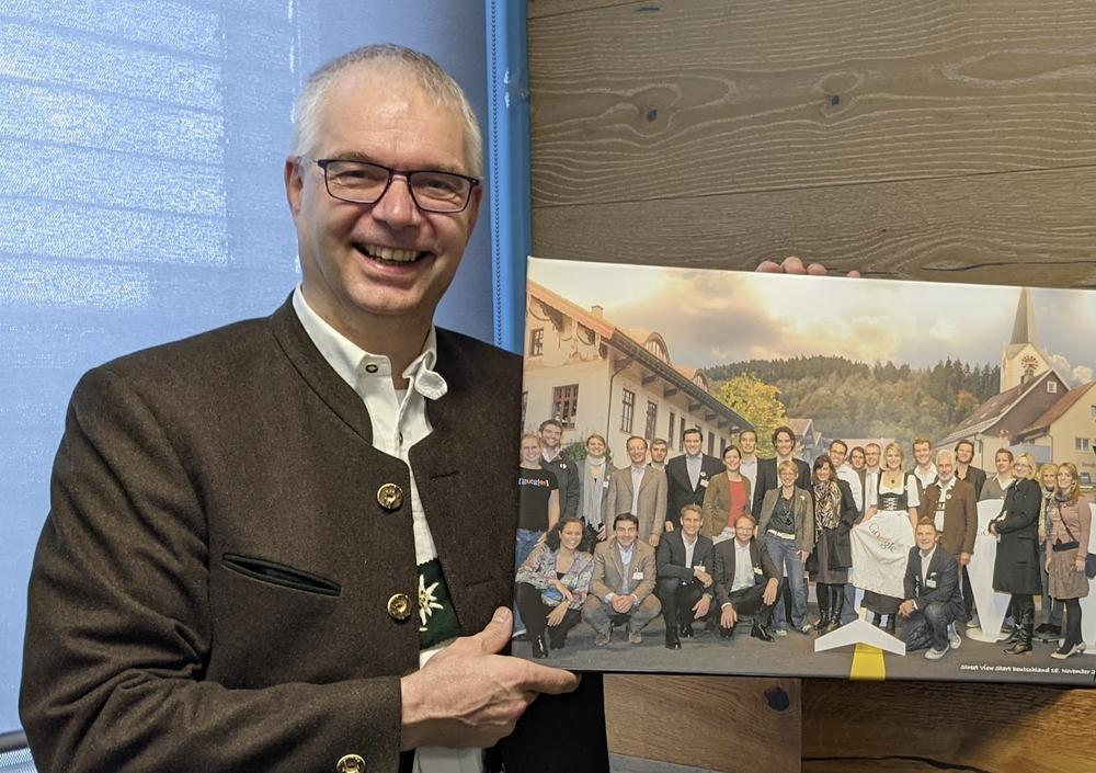 Ein Foto von Wieland Holfelder heute, der ein Bild von dem Event in Oberstaufen in den Händen hält