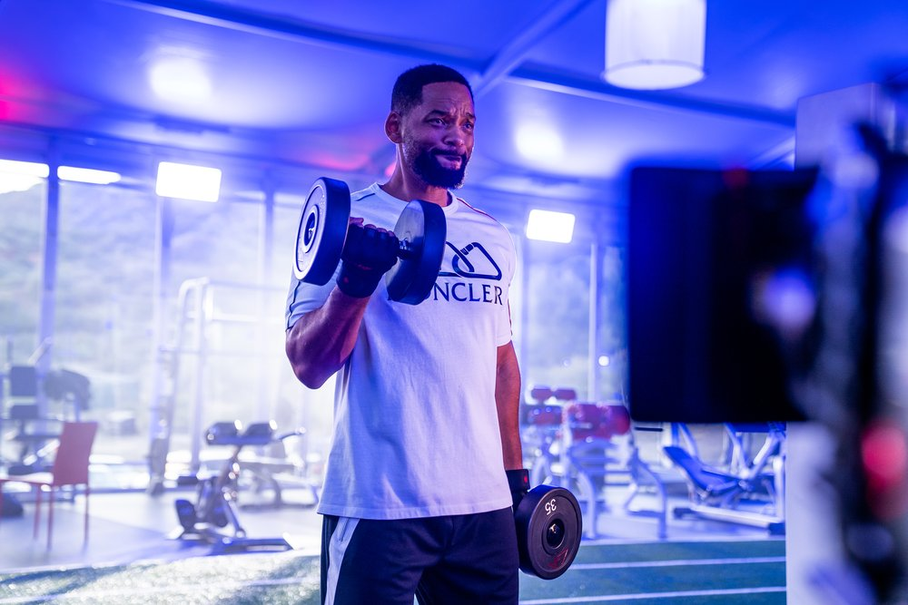 Will Smith does bicep curls with two dumbbells in a gym, wearing a white t-shirt and black shorts.