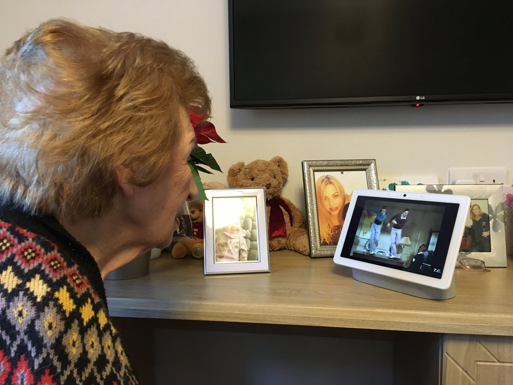 An elderly woman with brown hair wearing a sweater looks at Nest Hub Max screen that's playing a video of people tap dancing on it. The device is sitting on a table where she also has family photos in frames.