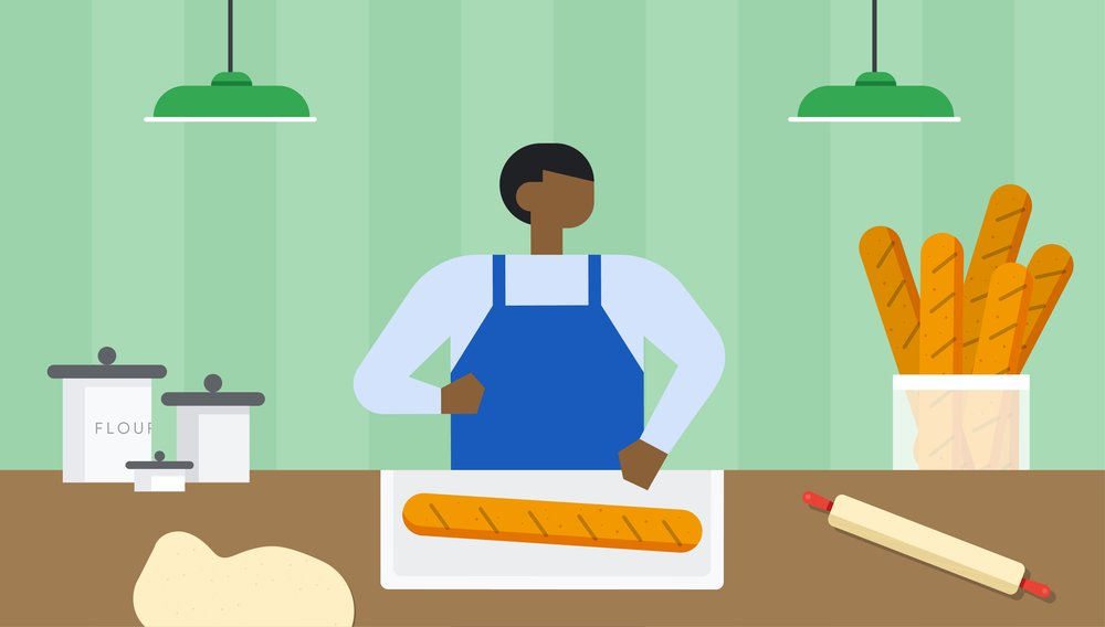 An illustration of a person in a blue apron standing behind a table and in front of a green wall. The table has jars of flour, a rolling pin, some dough and a loaf of baked bread sitting on a cutting board.