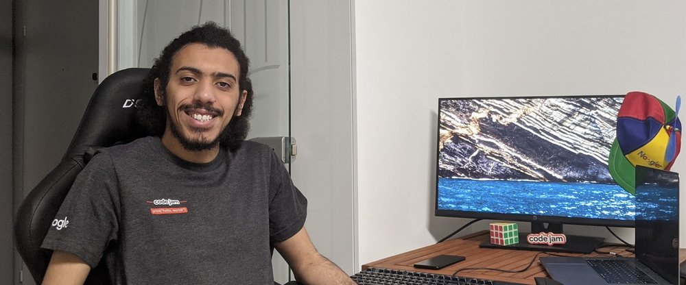Article's hero Yosri sitting at his desk at home while wearing a Code Jam shirt. On the desk are a monitor, a laptop, a phone, a Rubix cube and a Noogler hat.media