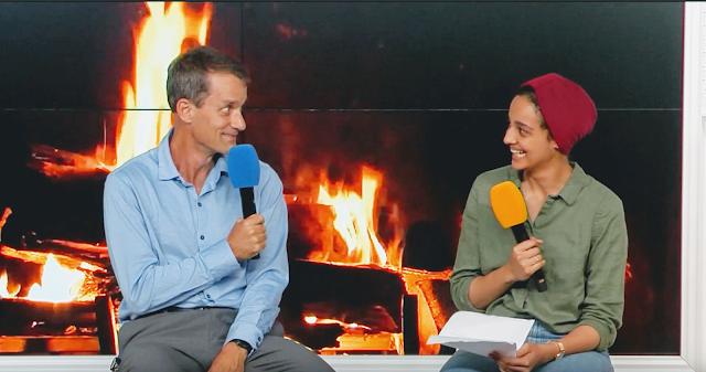 Nada interviewing Google Senior Fellow Jeff Dean in front of an artificial fireplace.