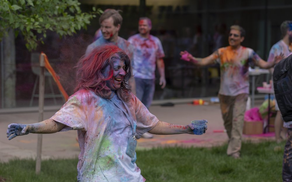 Photo of Bhavna smiling at a Holi celebration; she is covered in different colored powders, and people around her are as well.