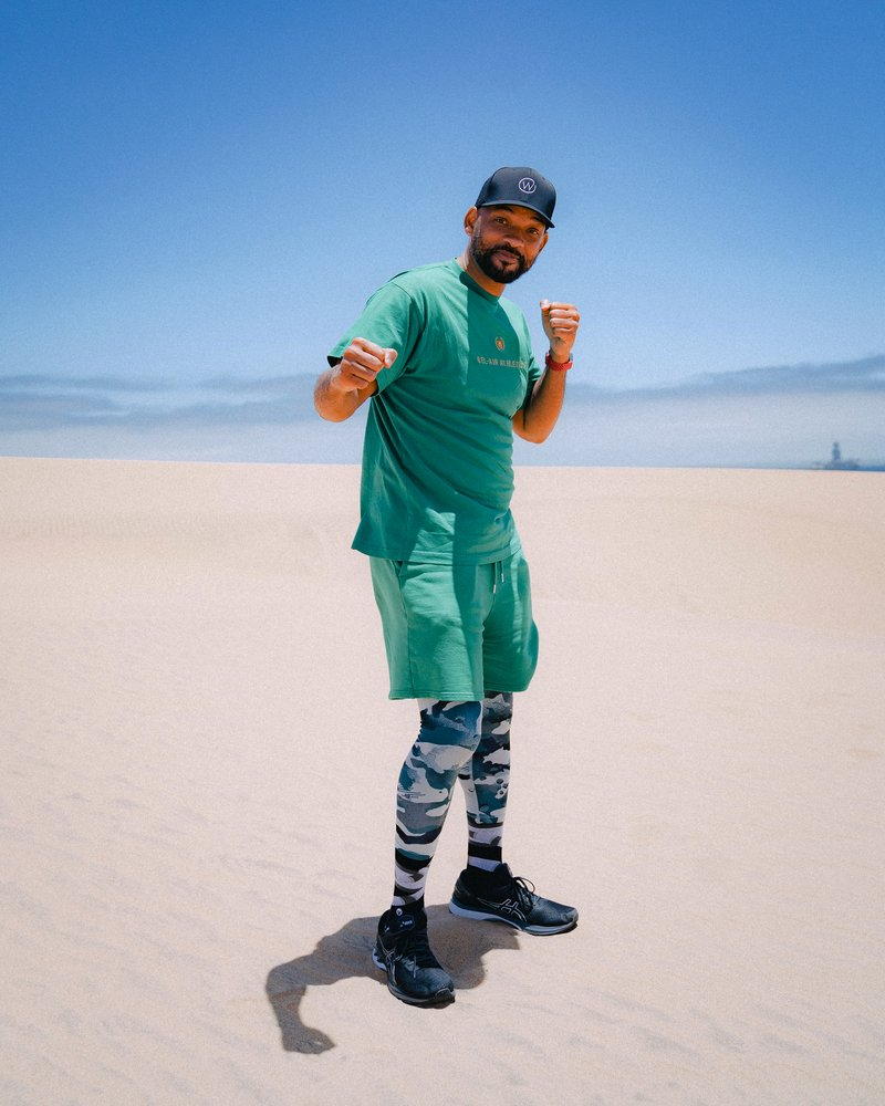 Will Smith wearing Fitbit Charge 4, green shorts, a green shirt and camouflage leggings, takes a boxing stance in the sand dunes.