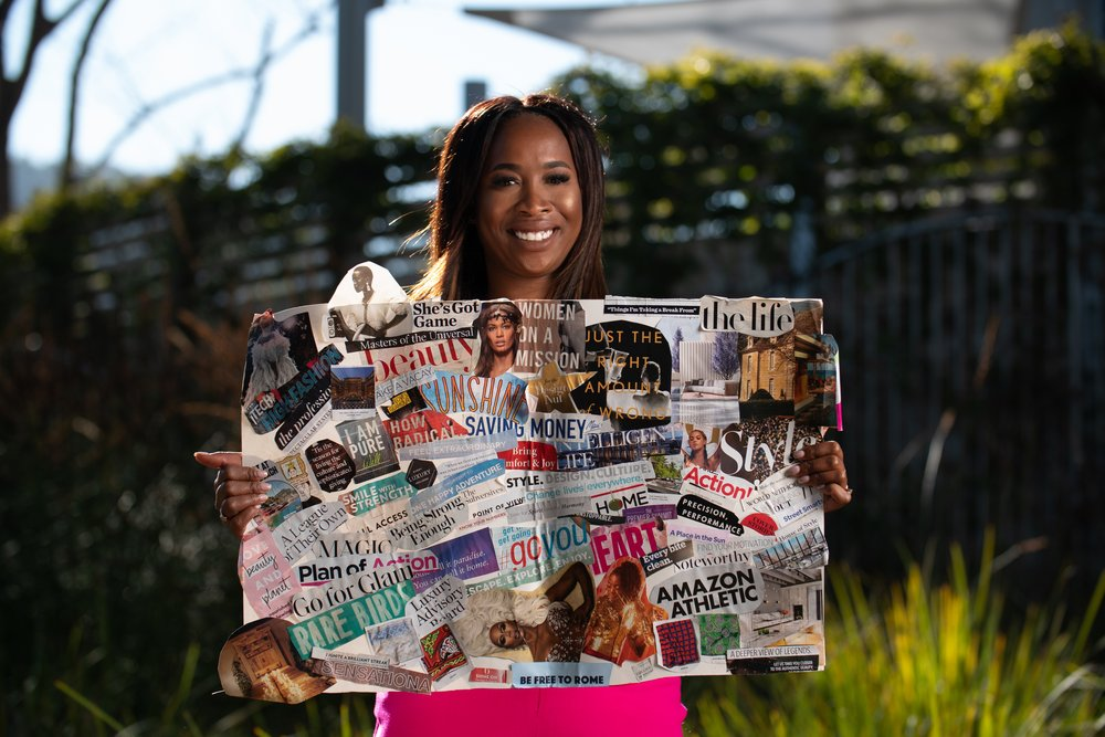 Annie Jean-Baptiste holding vision board while standing outside.