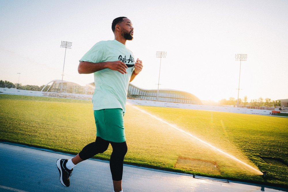 Will Smith running on a track, wearing green running shorts and shirt, and Fitbit Charge 4.