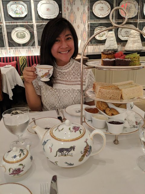 Alison holding a tea cup sitting indoors with a teas set on her table.