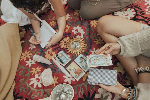 People seated in a circle on a red print carpet around Tarot cards and crystals.