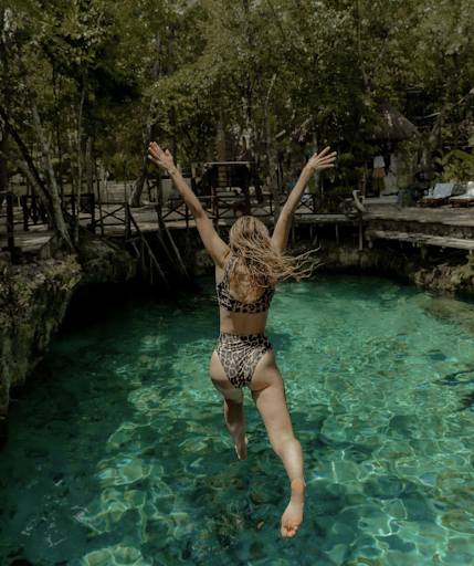 Andi wears a two-piece leopard-print swimsuit as she leaps into a green pool of water