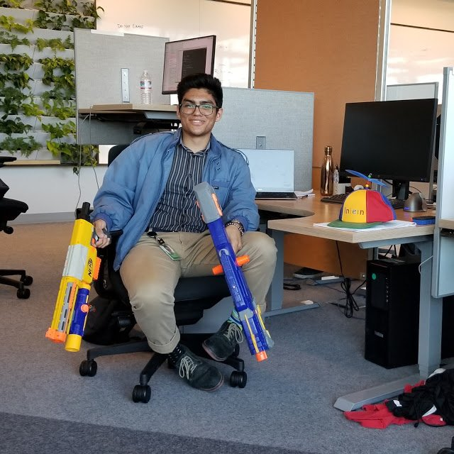 Robert at his desk holding two nerf guns.