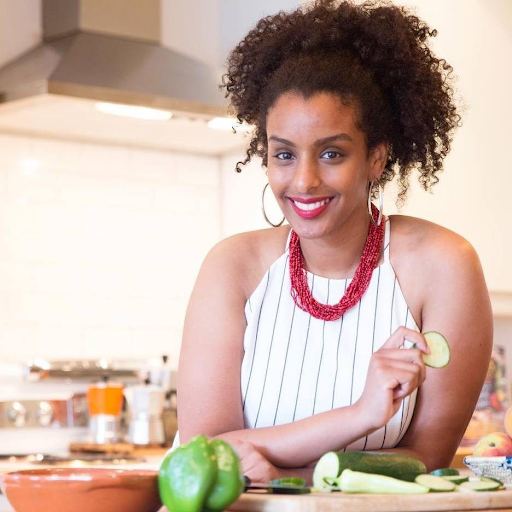 Black Foodie founder Eden Hagos smiles in a white halter top with red necklace, hoop earrings and upswept hair, as she chops green veggies at the kitchen counter.