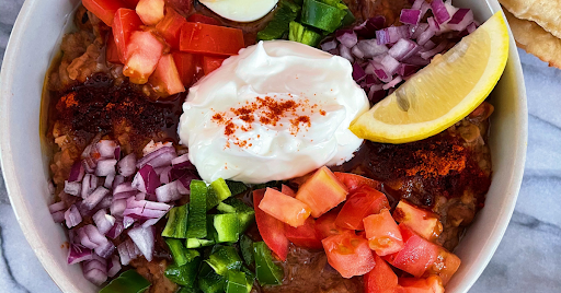 A colorful stew of fava beans, red onions, tomatoes and jalapeno peppers, topped with yogurt, cumin and lemon.