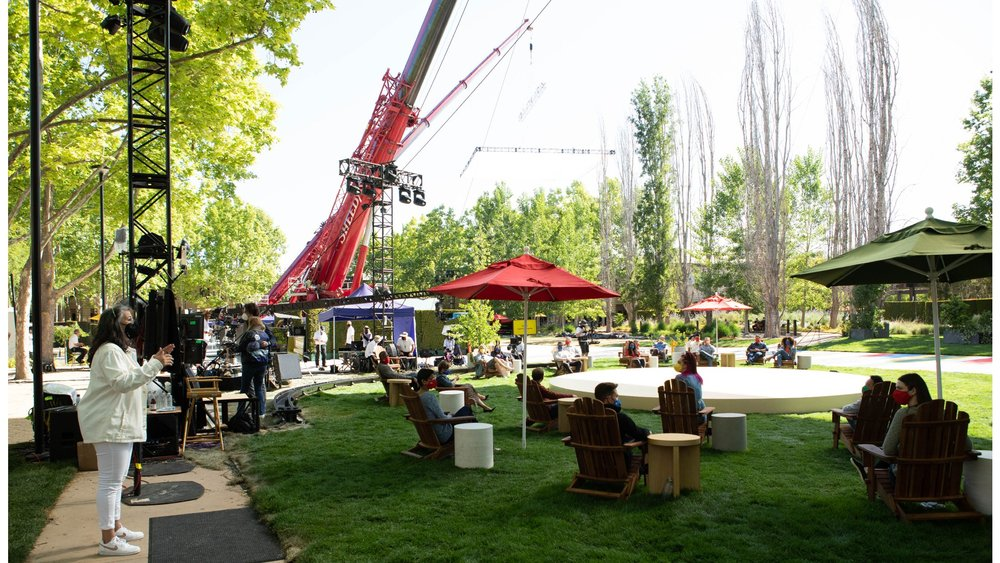 """Photo showing the """"quad"""" at Google's Mountain View campus. People wearing masks are sitting in chairs on the lawn around a circular stage; a large crane is visible in the background."""