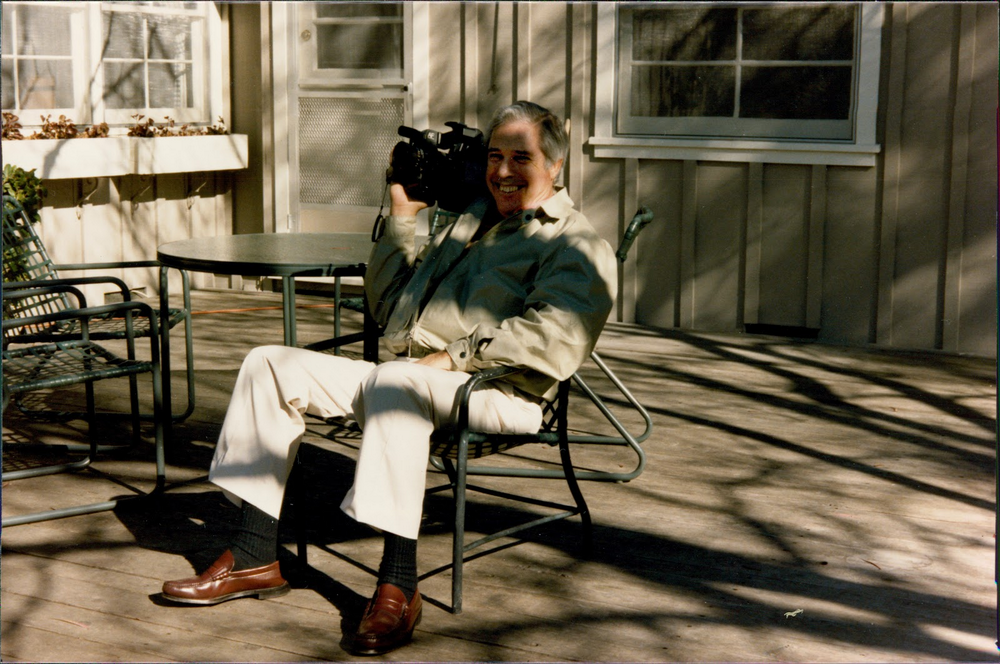 Author's grandfather sits on am outdoor bench with a camcorder over his shoulder.