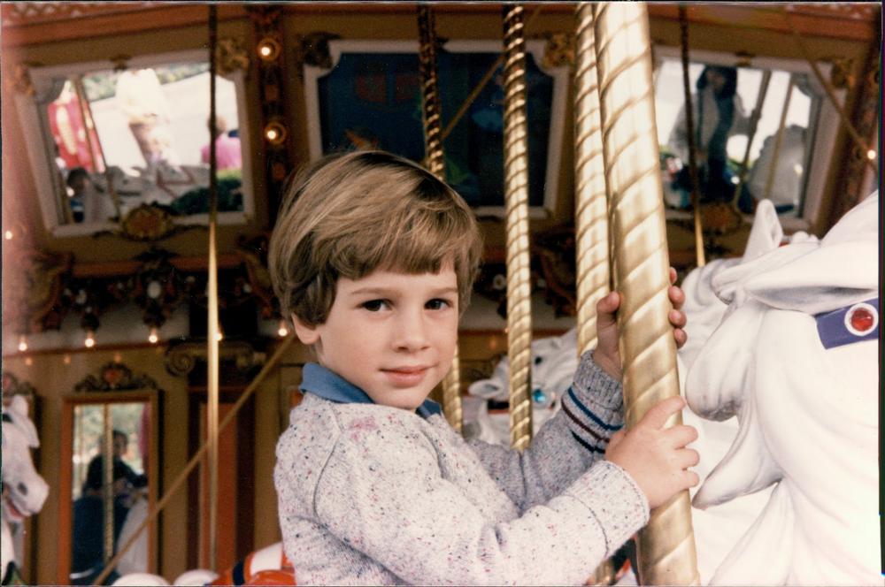 Photo of author riding a merry-go-round.