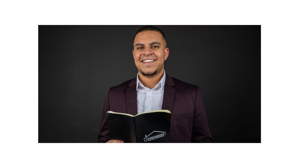 """Image showing a man in a suit holding a book that says """"CodeHouse"""" on it. He is looking into the camera and smiling."""