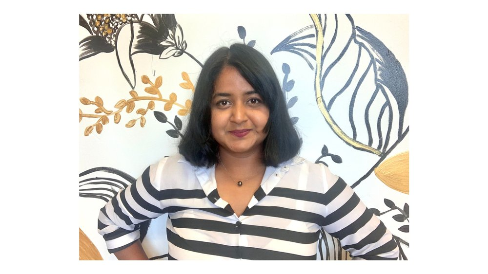 Debbie Biswas is smiling and facing the camera with shoulder length black hair wearing a white and black striped shirt in front of a wall with floral patterns.
