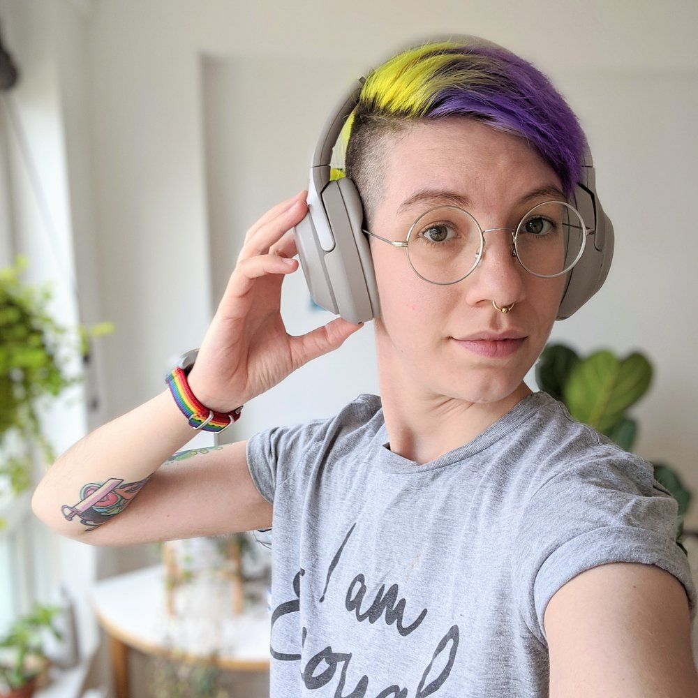 """Androgynous thin white person with short hair dyed purple and yellow. They wear noise cancelling headphones and a grey t-shirt that says """"I am enough"""". Lio also wears round glasses and a watch with a rainbow strap. Their right hand is reaching up to their headphones, revealing a Steven Universe tattoo. They look proud and optimistic. In the background are plants and sunlight shines through a window."""