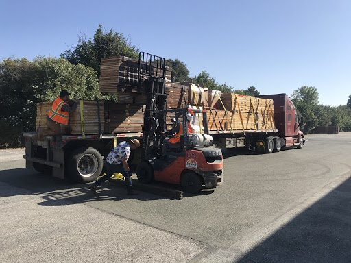 A fork lift loads stacks of wood doors onto the back of a truck to get ready for donation.