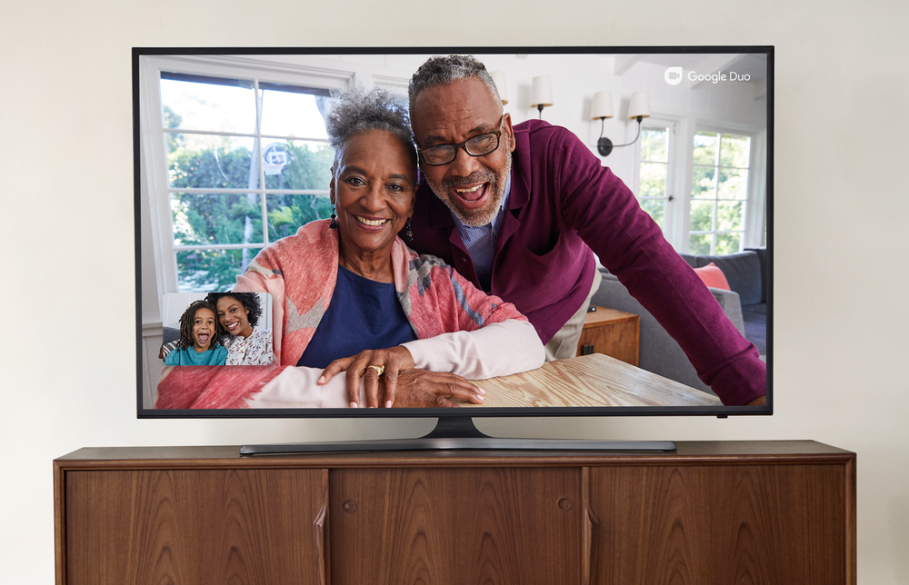 Image showing two grandparents looking out from a television screen, while picture-in-picture in the lower left-hand corner of the screen shows a mother and daughter talking to them.