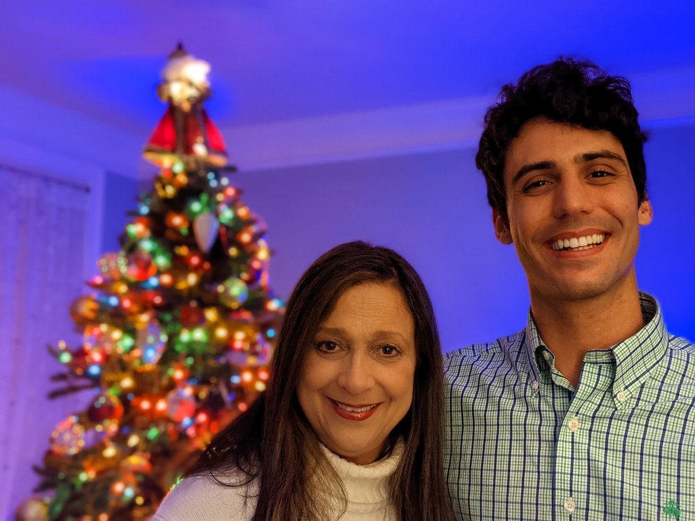 Image showing the author with his mother in front on a decorate tree in a dark room. The subjects are well-lit and in focus while the background is blurred.