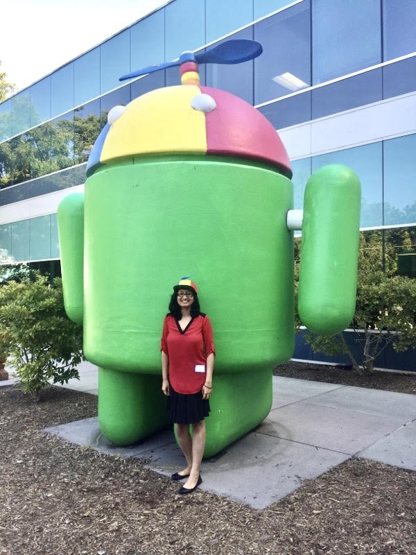 Preeti standing in front of a large Android statue wearing a Noogler hat.