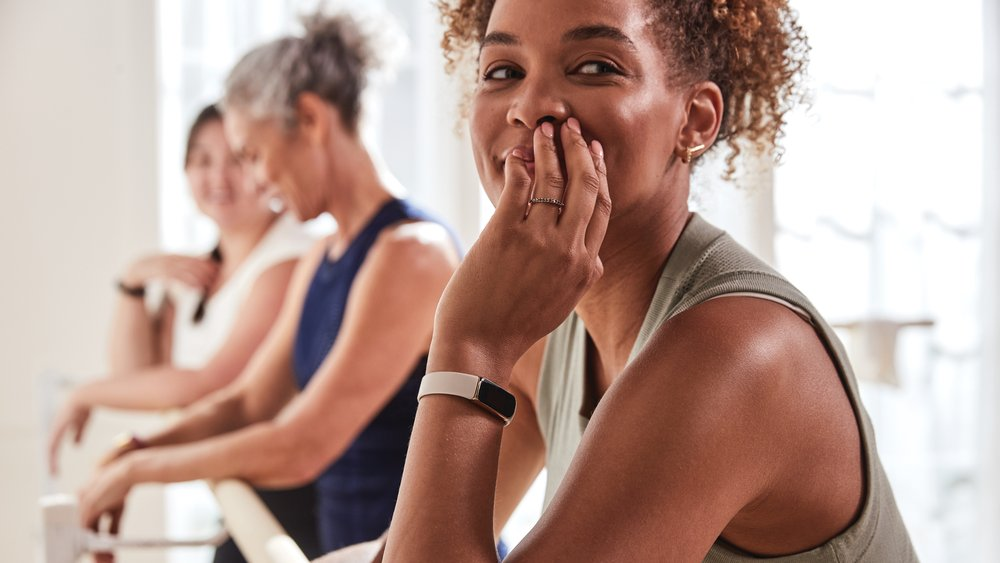 A woman wearing a Fitbit Luxe tracker leaning on a ballet barre with her fingers touching her face; two other women, out of focus, are also leaning on the barre in the background.
