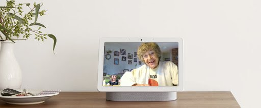 Image showing a Nest Hub Max sitting on a table. On the screen is an older women, looking out, smiling; in a small, picture in picture screen in the corner is a younger woman, smiling.