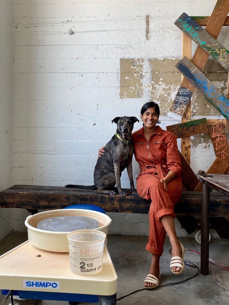 Gopi Shah seated with and her dog, Hanz, in their Long Beach Studio, next to her pottery equipment.