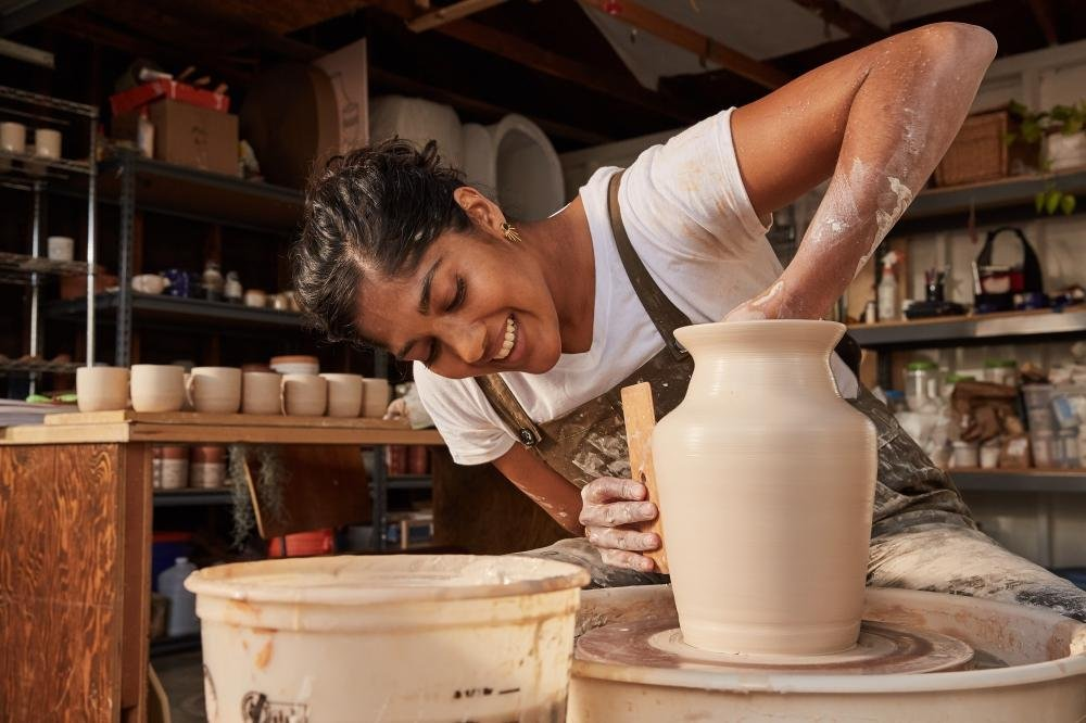 Gopi Shah in her studio, shaping a clay pot.