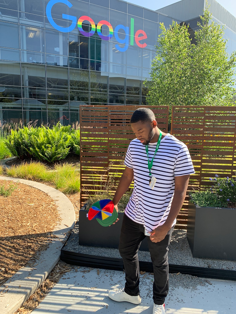 Grant standing in front of Google sign at headquarters holding his Intern hat.