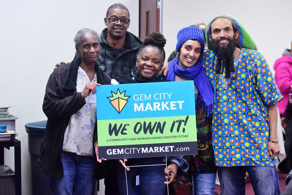 A group of people holding a sign advertising Gem City Market in Ohio