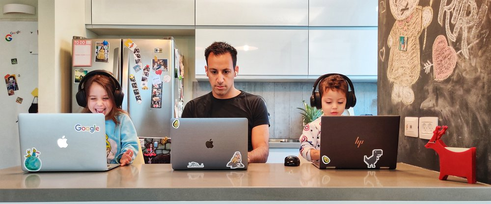 Asaf and his two kids all working at their laptops at the kitchen counter.