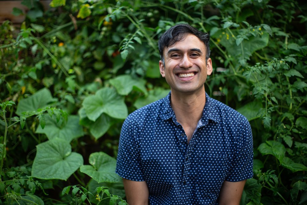 A man standing in front of greenery, smiling at the camera.