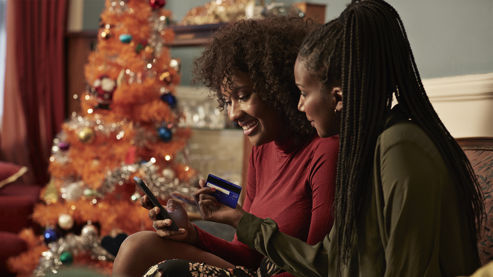 Two Black women sit on their couch at home online shopping together. One woman holds her phone while the other woman looks on and holds her credit card. There is an artificial orange Christmas tree in the background.