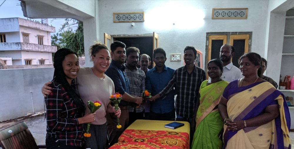 From left to right, Diana and Courtney are pictured holding flower bouquets gifted to them by the farmers they're pictured with, as they visited the farmers they work with in Vijayawada, India to observe an information exchange.