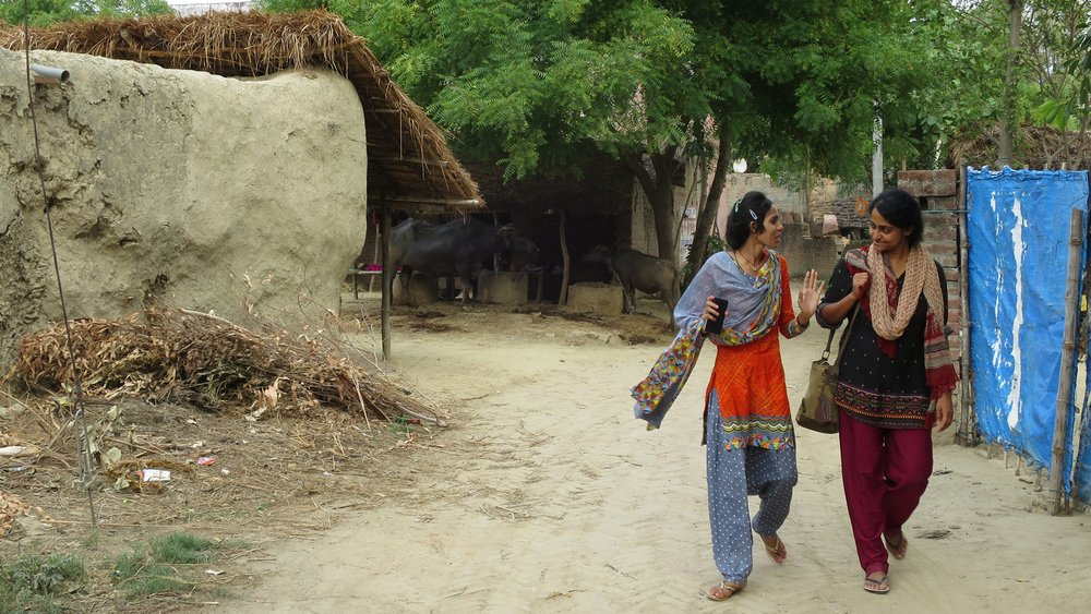 Nithya walking down a road with another person while working in the field.