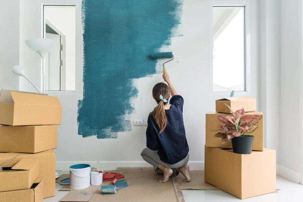 A woman is painting a blank white wall blue, surrounded by moving boxes and a plant
